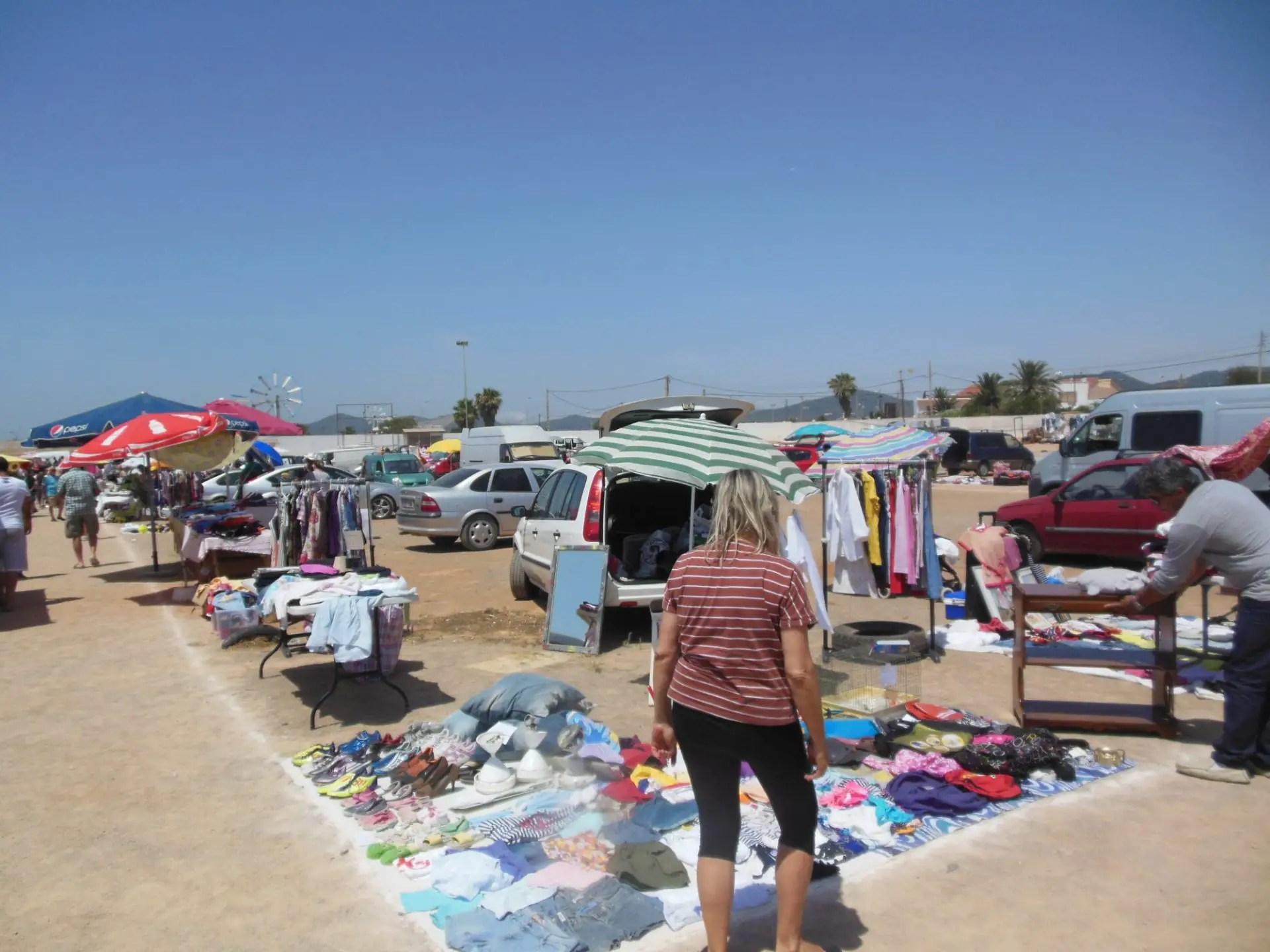 De Hipodromo in Sant Jordi veranderd in een markt - vrouw kijkt naar de kleding uitgestald op een kleedje