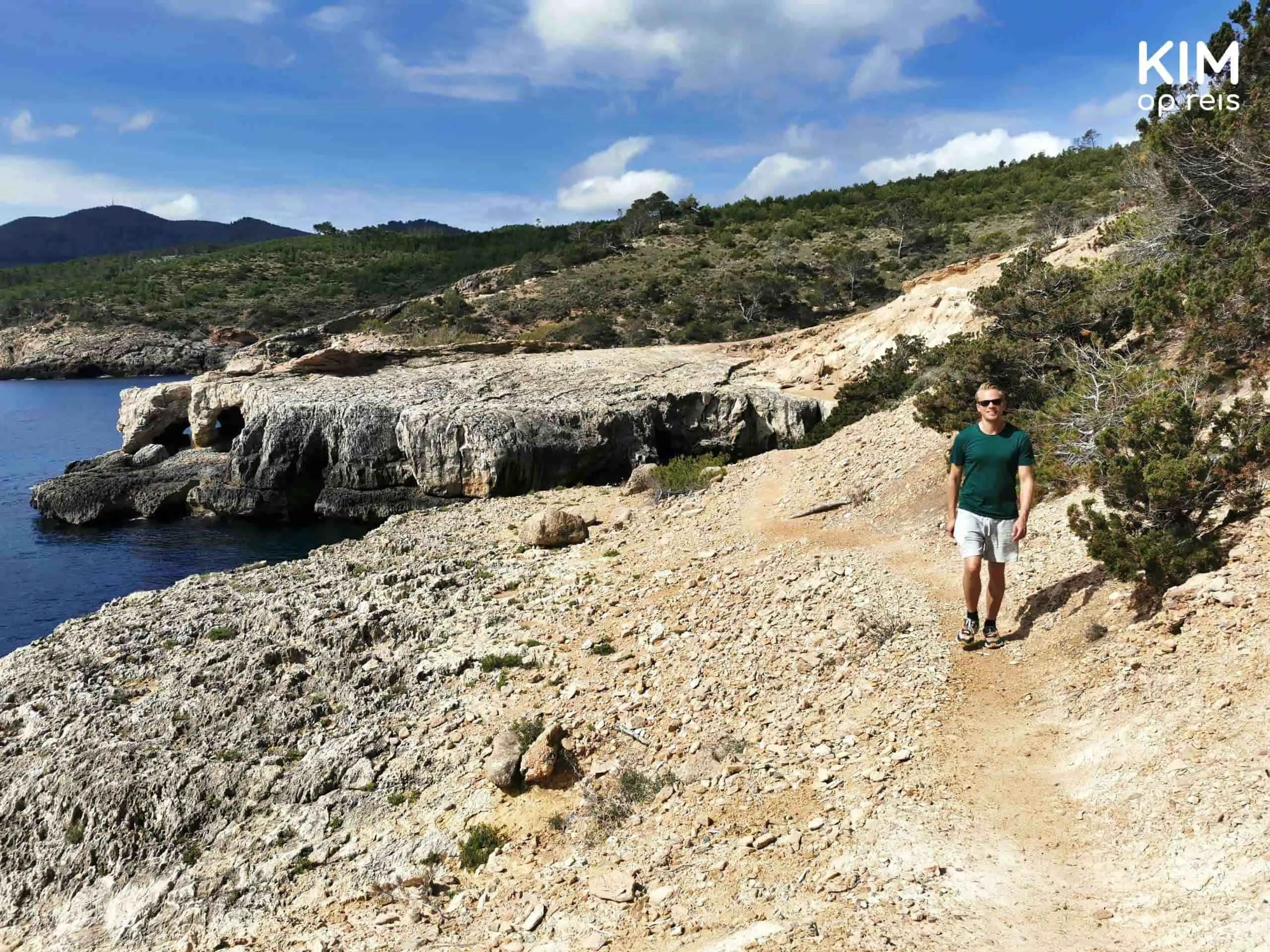 Cova d'en Jaumet walk: man follows a path along the coast