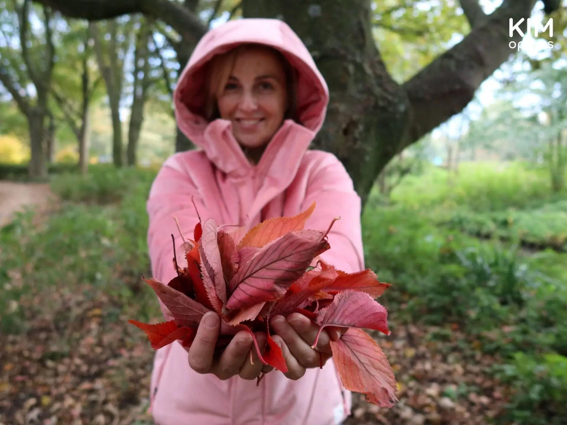 Duurzame winterjas Protest: Kim in roze jas met in haar handen rood roze herfstbladeren