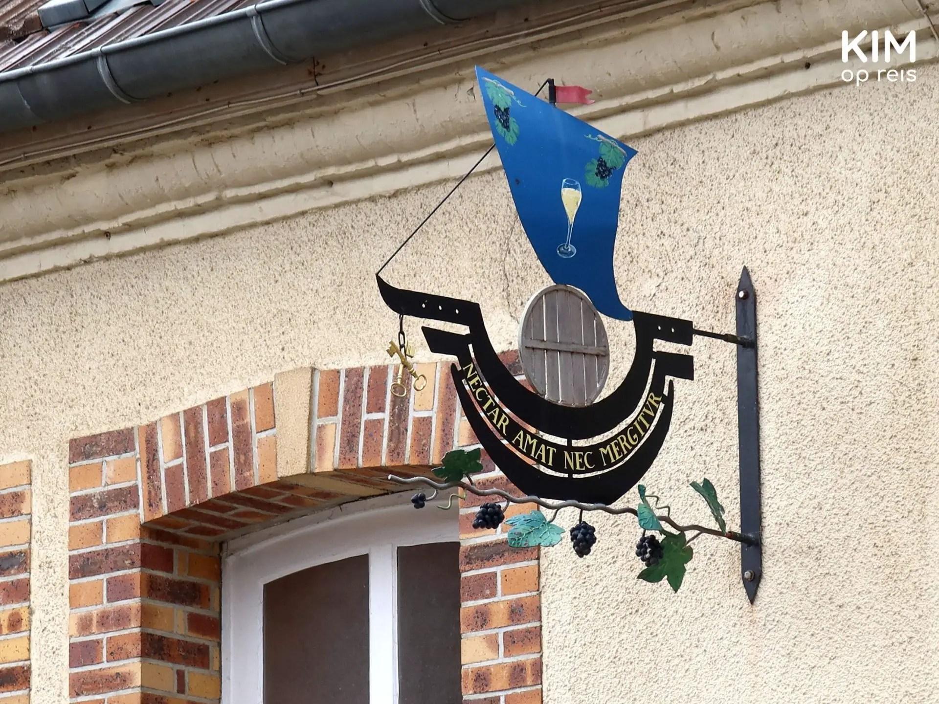 Hautvillers uithangbord: bordje met de deksel van een wijnvat en daarboven een blauwe vlag met een glas champagne
