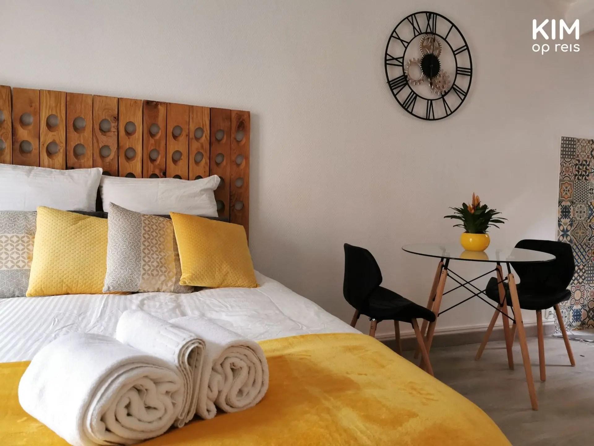 Studio Epernay bed overnachten: deel van het tweepersoonsbed met een zitje ernaast, gele details