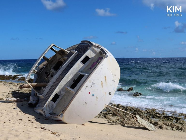 Stranded sailing yacht on the island: small sailing yacht lying on its side on the beach