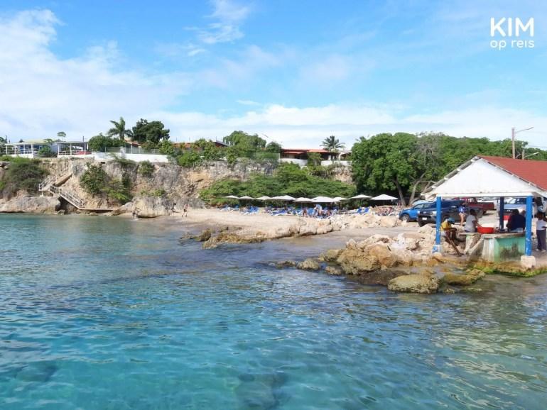 Playa Grandi Playa Piskadi Curaçao: het strand vanaf de pier met rechts het vissershutje, dan de parkeerplaats en vervolgens een tiental strandparasols met bedjes
