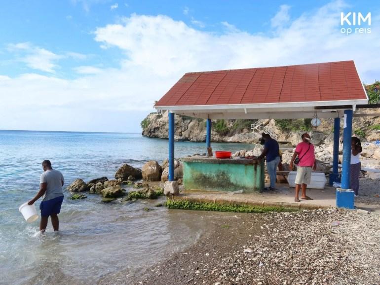 Playa Grandi vissers maken vis schoon: een overdekte vissershut met een werkplaat waar enkele vissers staan te werken