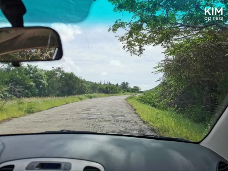hobbelige weg naar Porto Marie: foto van slecht wegdek vanuit de auto
