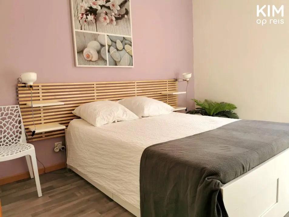 Airbnb Reims: slaapkamer met tweepersoons bed en een zachtroze muur met een schilderij