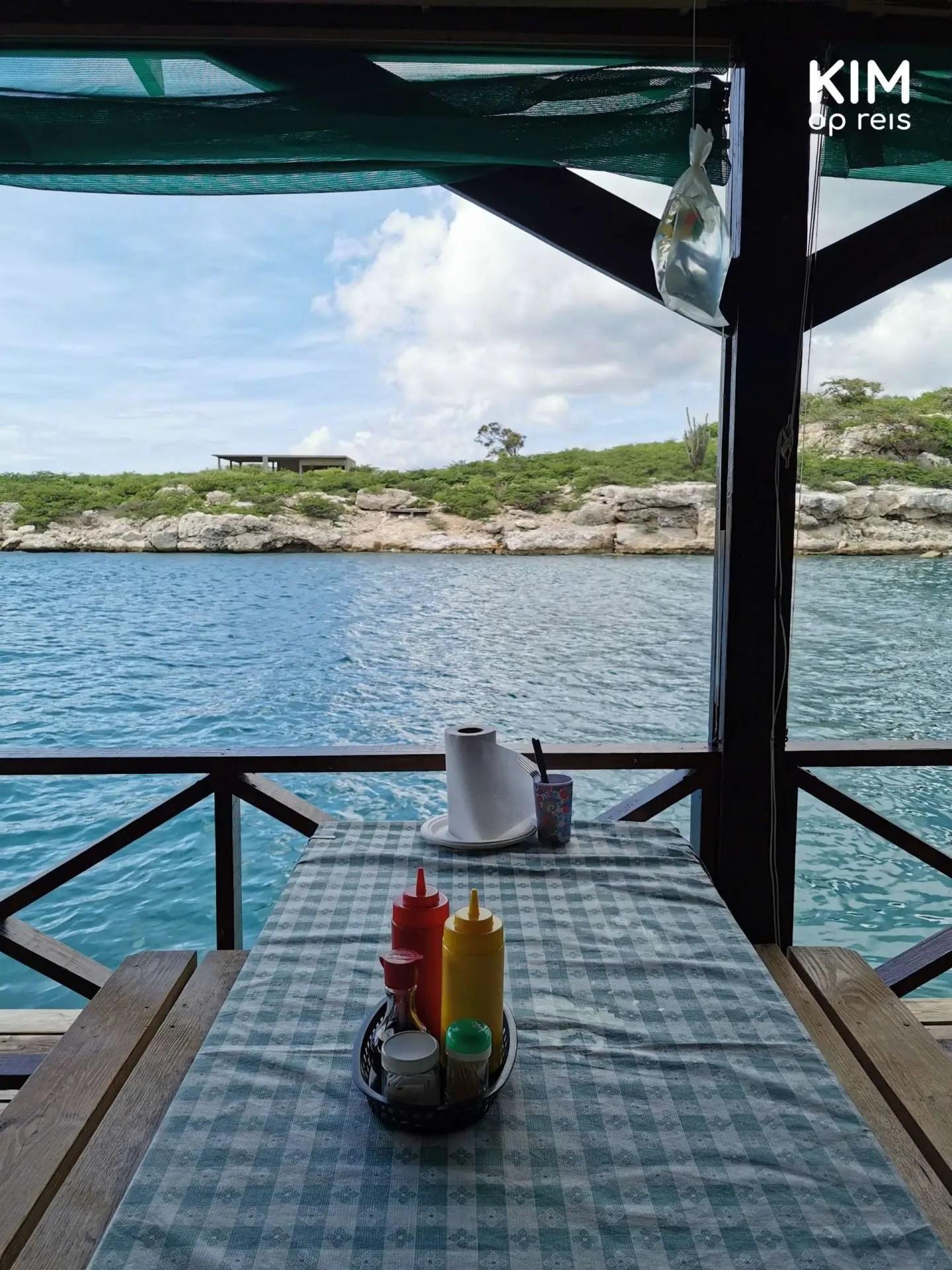 De Visserij uitzicht Curaçao: picknickbank direct aan het water, op tafel staan sausjes
