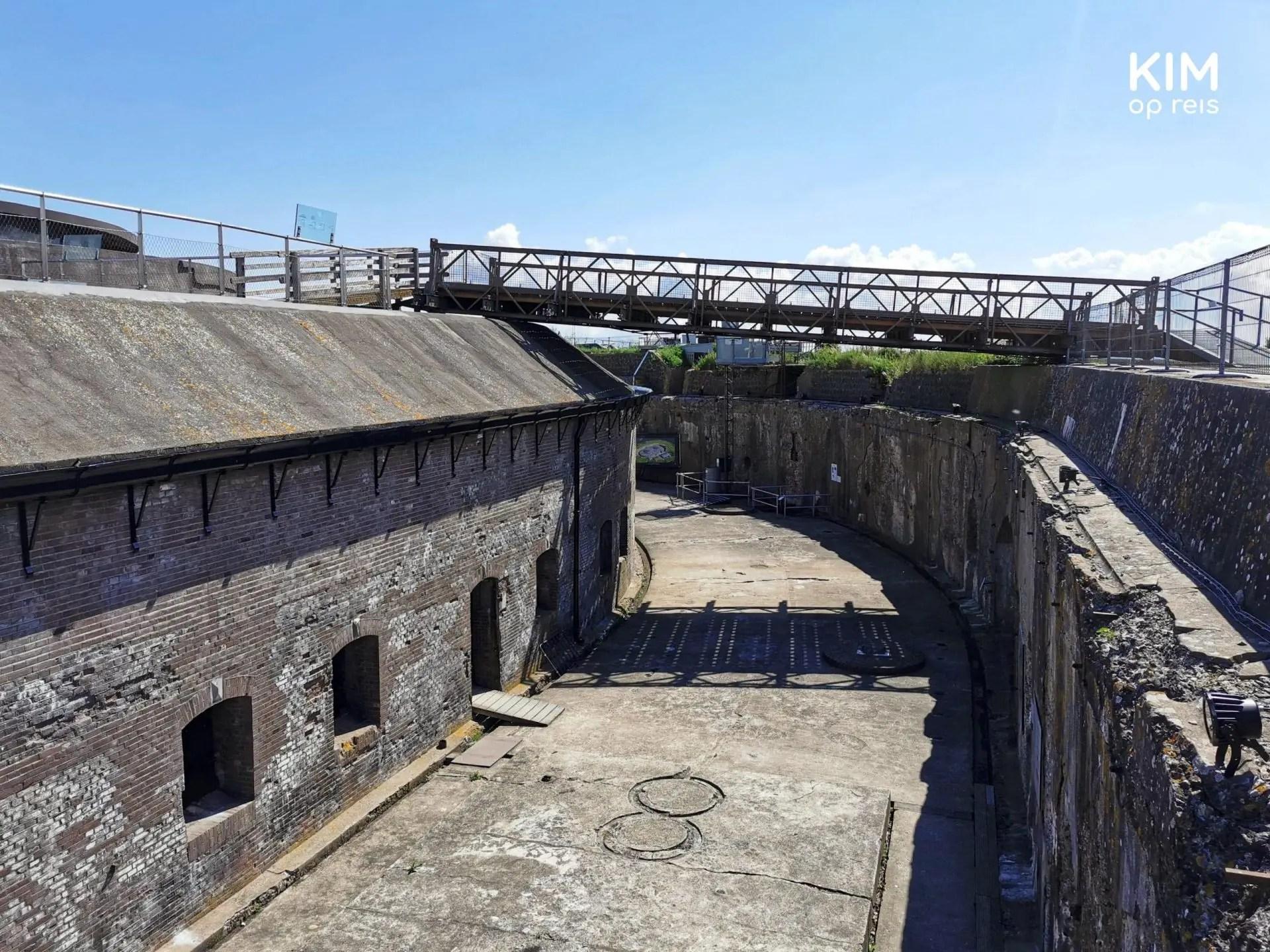 Forteiland Pampus bezoeken: het fort gezien vanaf een verhoging. Je kijkt op de brede wandelgang en een trap