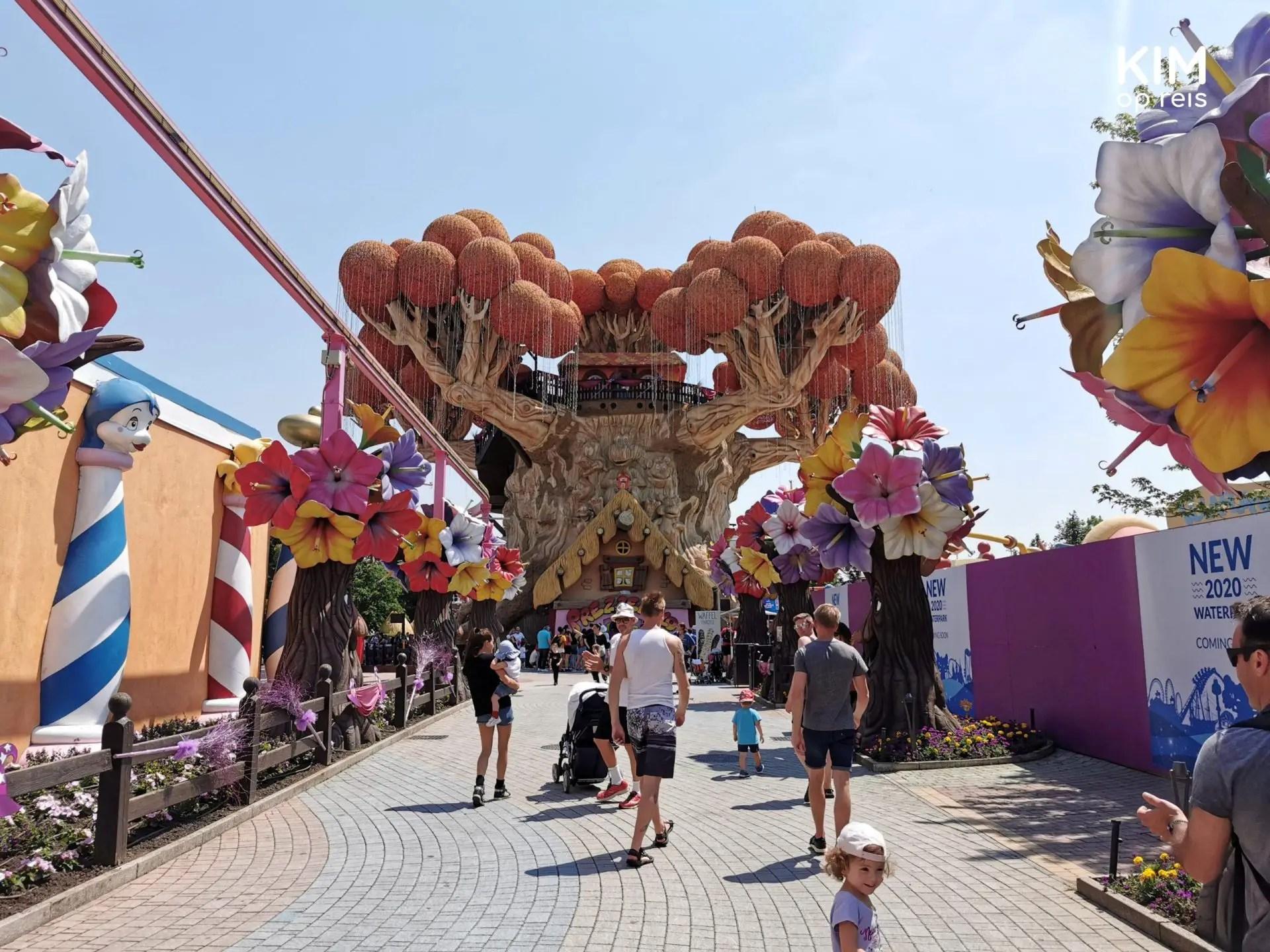 Gardaland attractiepark - entree van een themagedeelte vol kunsstof bloemen met enkele mensen die naar binnen lopen