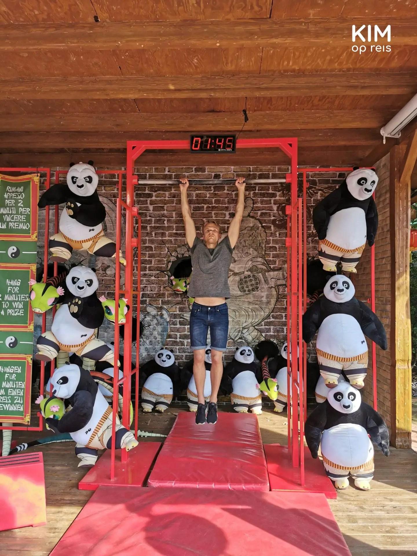 Gardaland spelletjes - man hangt aan ijzeren stang om een pandabeer te winnen