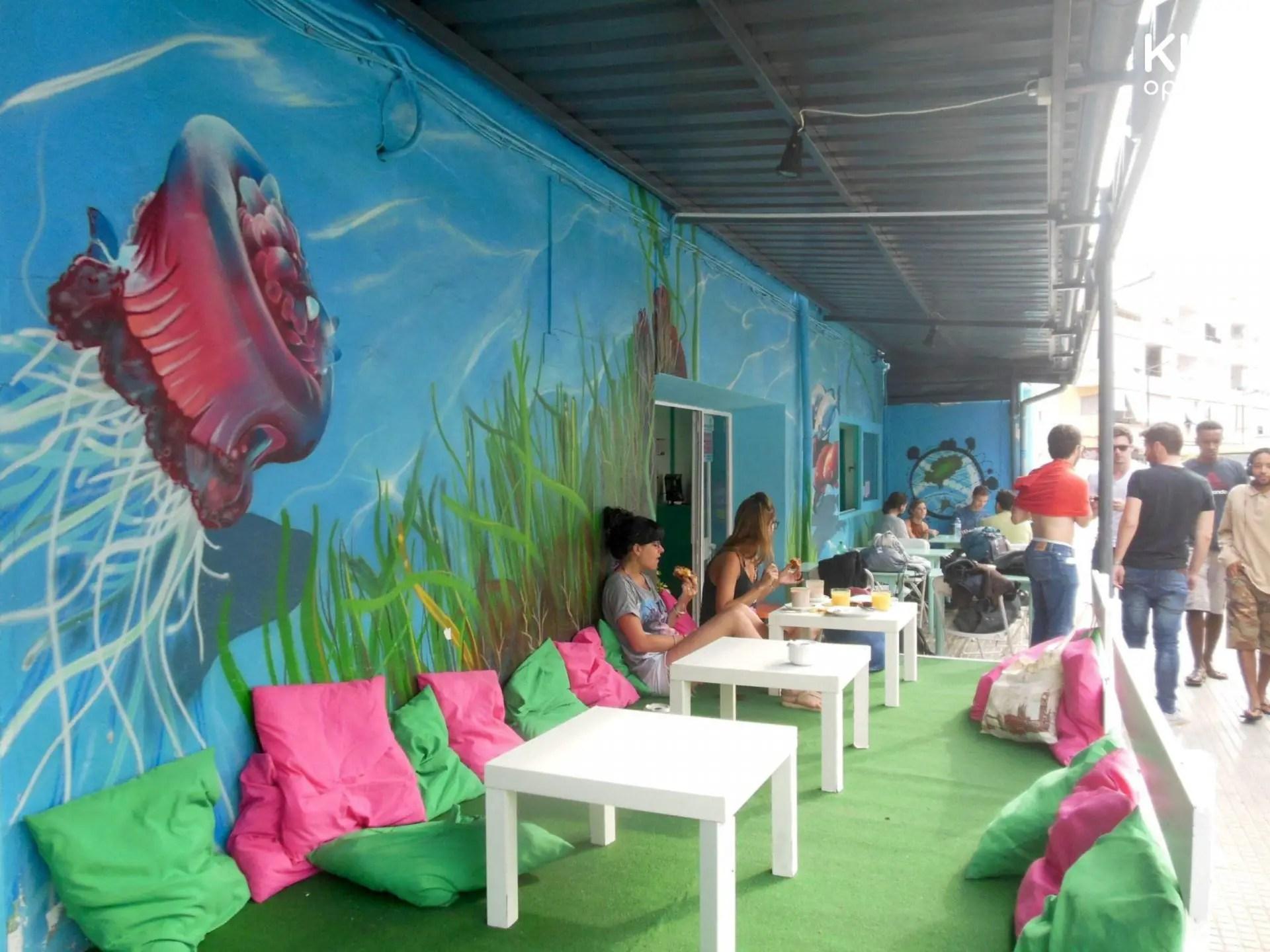 Terras van het Giramundo hostel - laag terras met kussen aan de straatkant