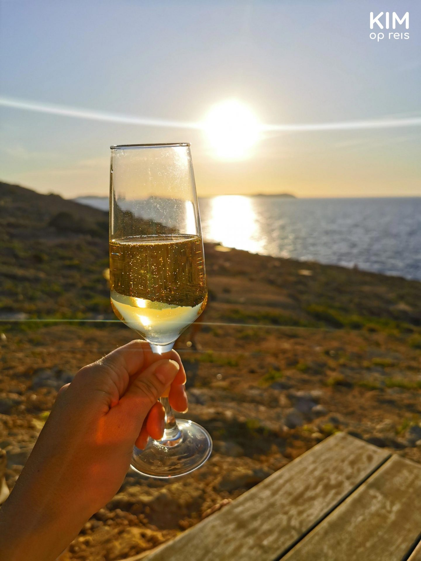 Toasting Hostal La Torre - hand with a glass of prosecco at sunset