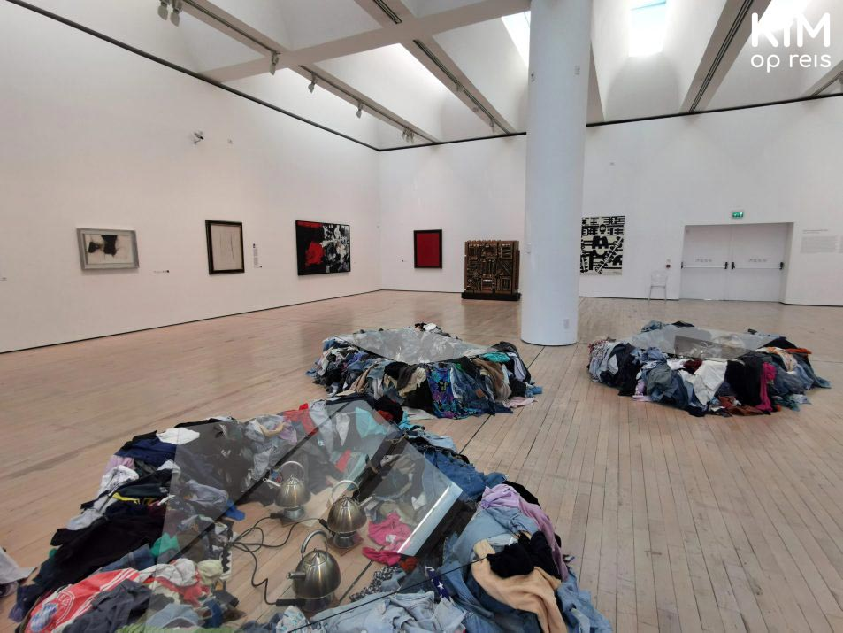 MART museum - piles of clothes with a glass plate on them in an exhibition space