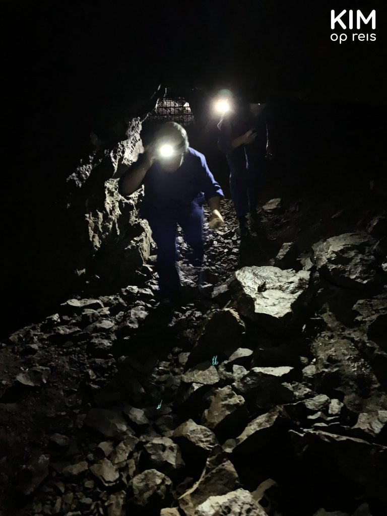 Mines Trento Monte Calisio: in the dark mine, someone walks in with overalls and a helmet with a light.