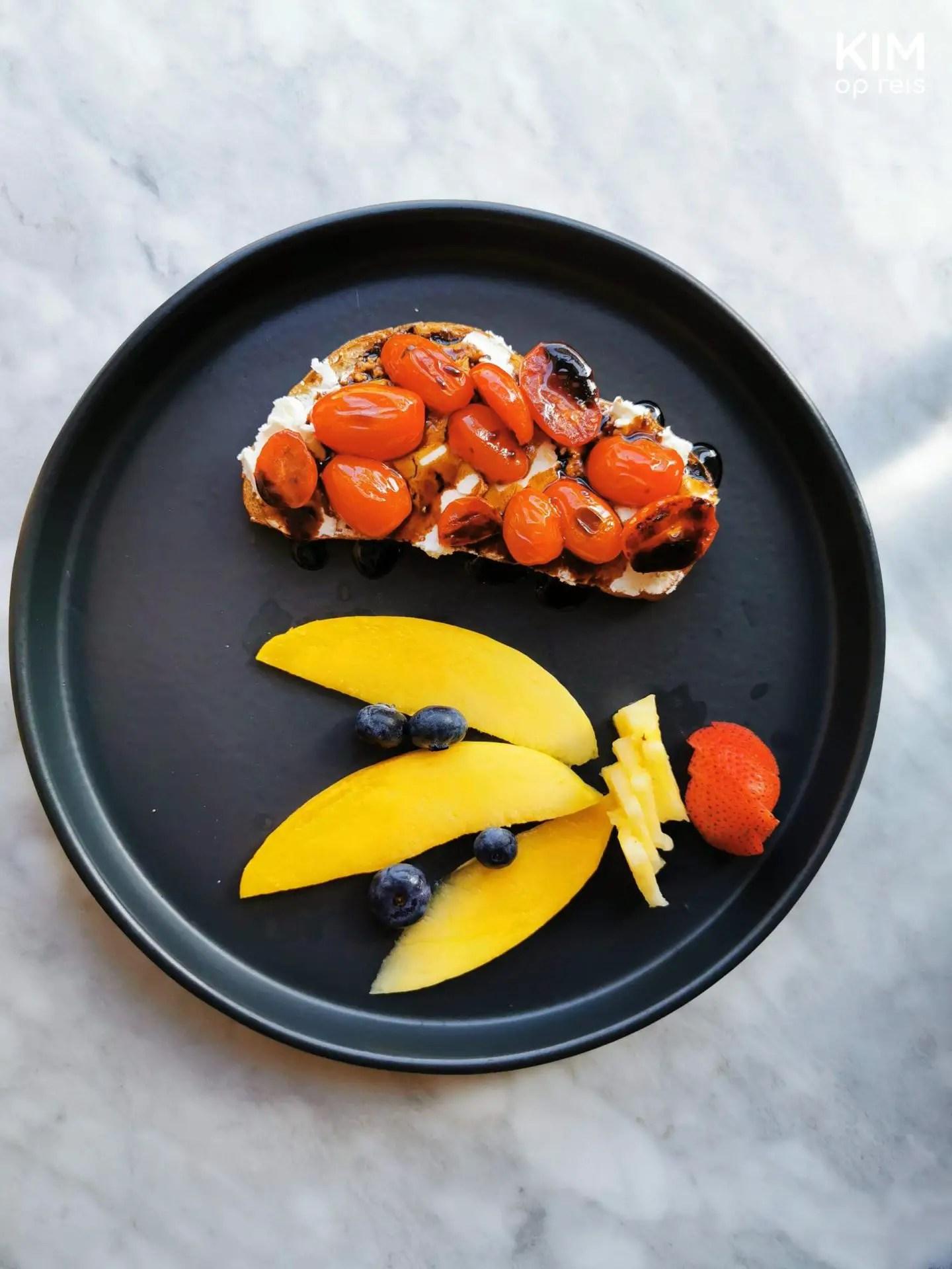 Ontbijten in Mérida: donker bord op een marmer ondergrond. Op het bord ligt een toast met witte kaas en tomaatjes en ernaast een garnering van fruit