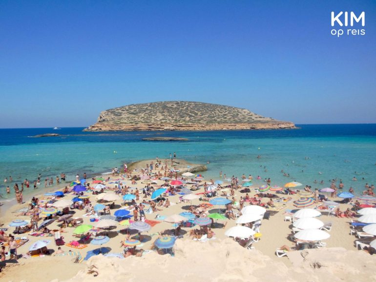 Beach Cala Conta Ibiza - colorful beach thanks to many tourists with umbrellas and an island in the distance in the water