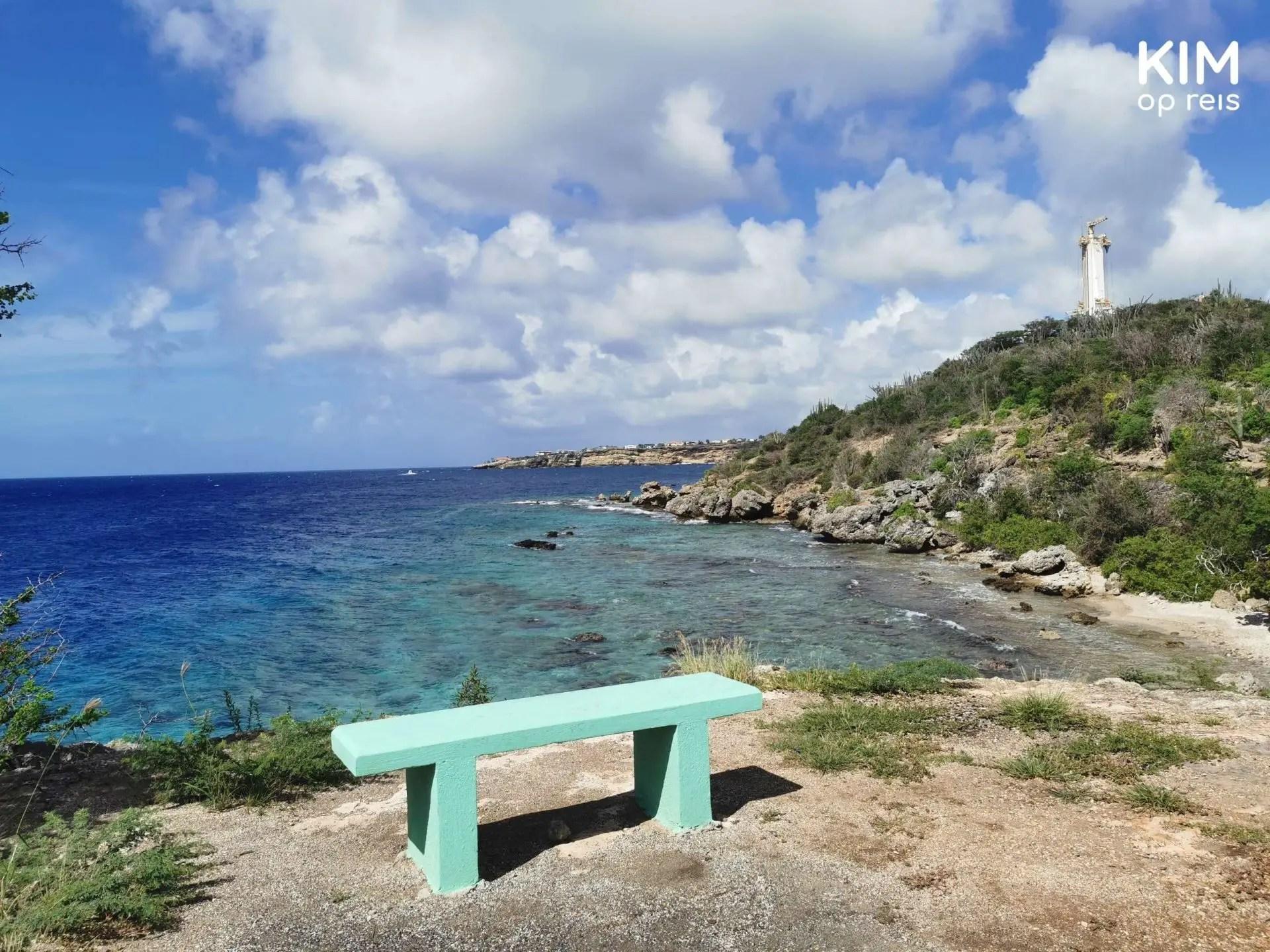 Uitzicht Direkteursbaai Oost Curaçao: mintgroen stenen bankje met uitzicht over het water en het land
