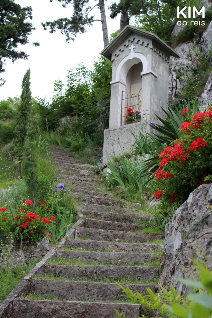 Valle dei Laghi walking tour - stairs up along flowers leads to a small altar