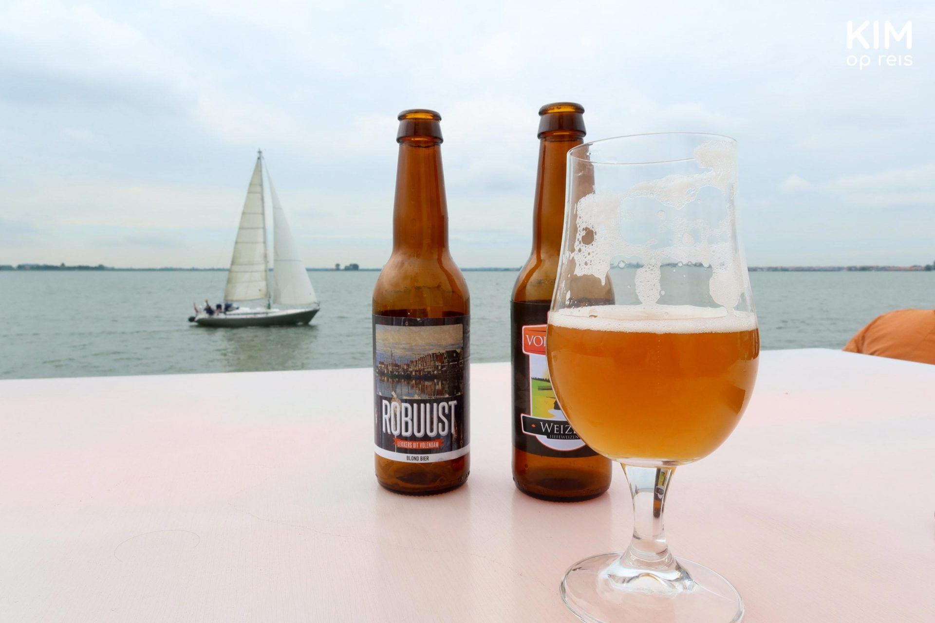Volendam beer on the Marken Express - 2 bottles of beer and a glass of beer on an elevation with a sailing boat in the water in the background
