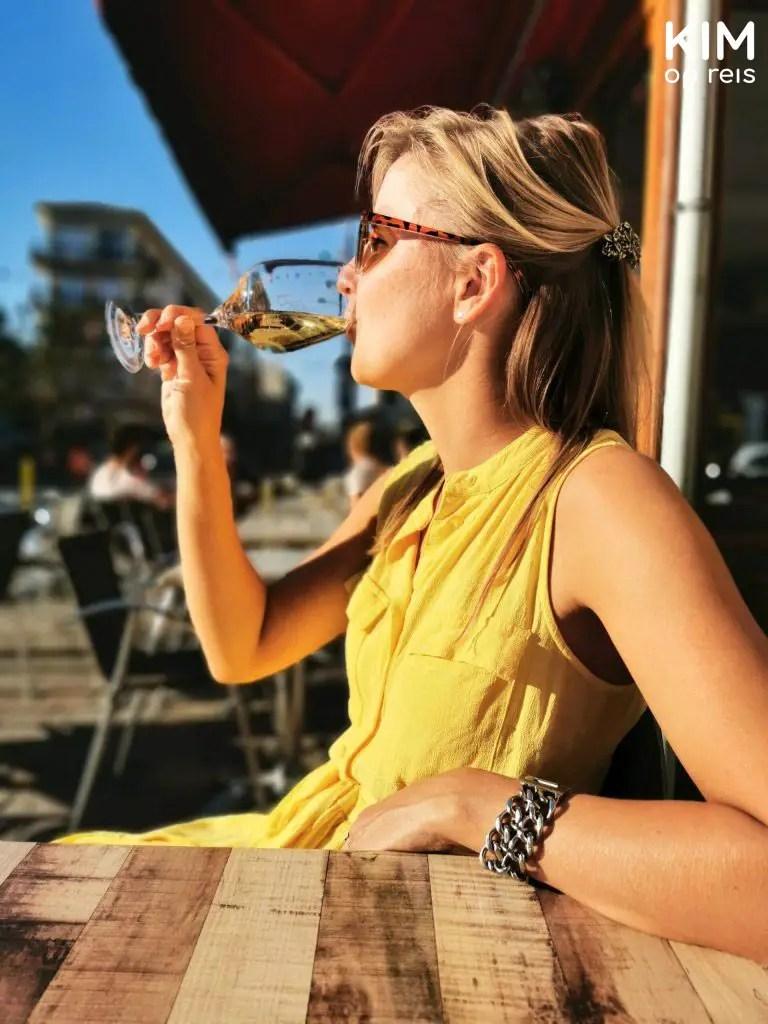 Wijn drinken BiBoViNo: Kim drinkt glas witte wijn en draagt een gele jurk
