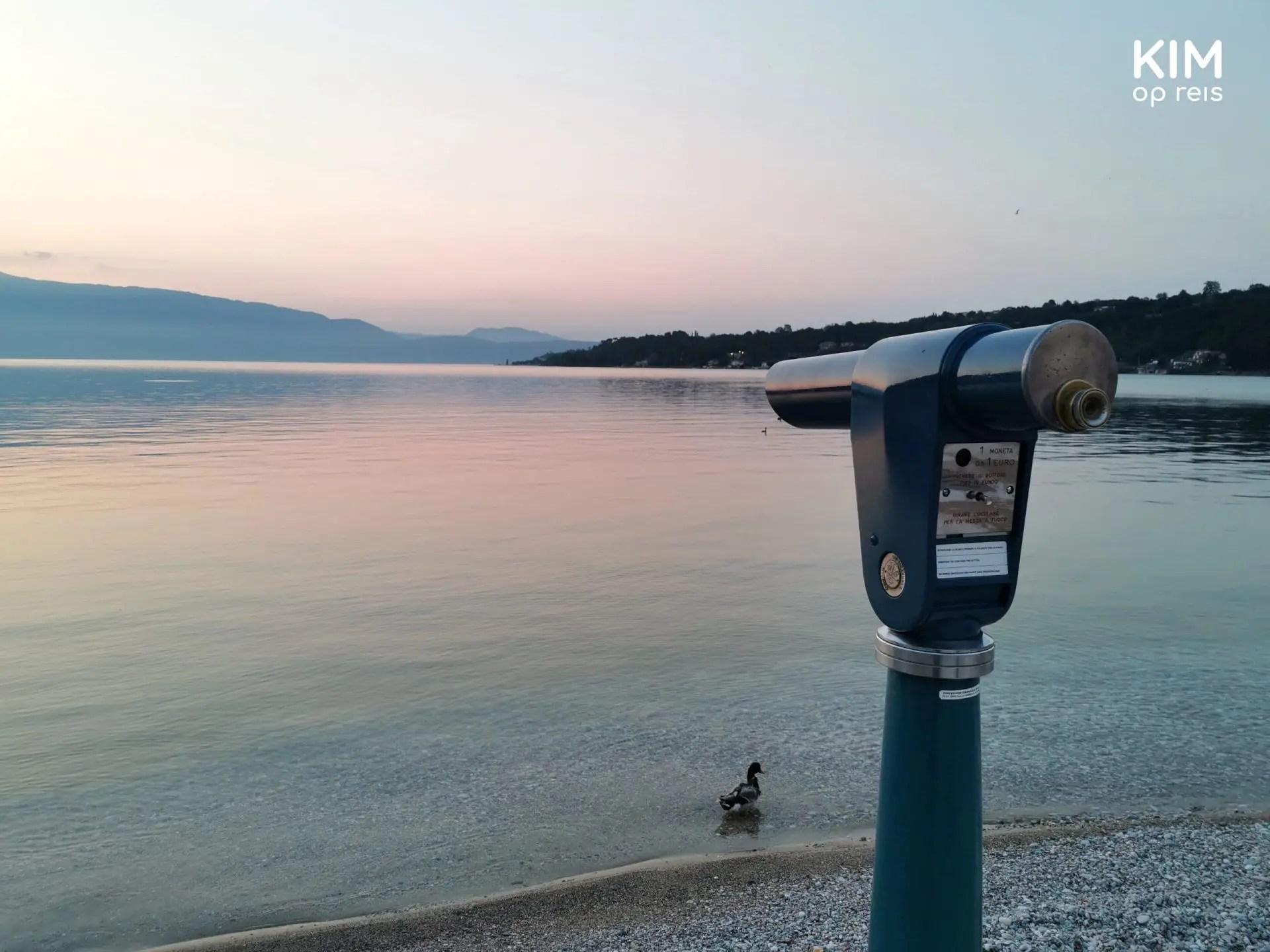 Zonsopgang Salò - uitzicht over het meer met een verrekijker rechts