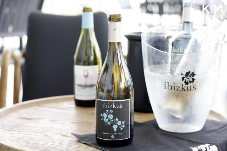 Wines by Ibizkus: two wine bottles on a table and two in a seethrough cooler