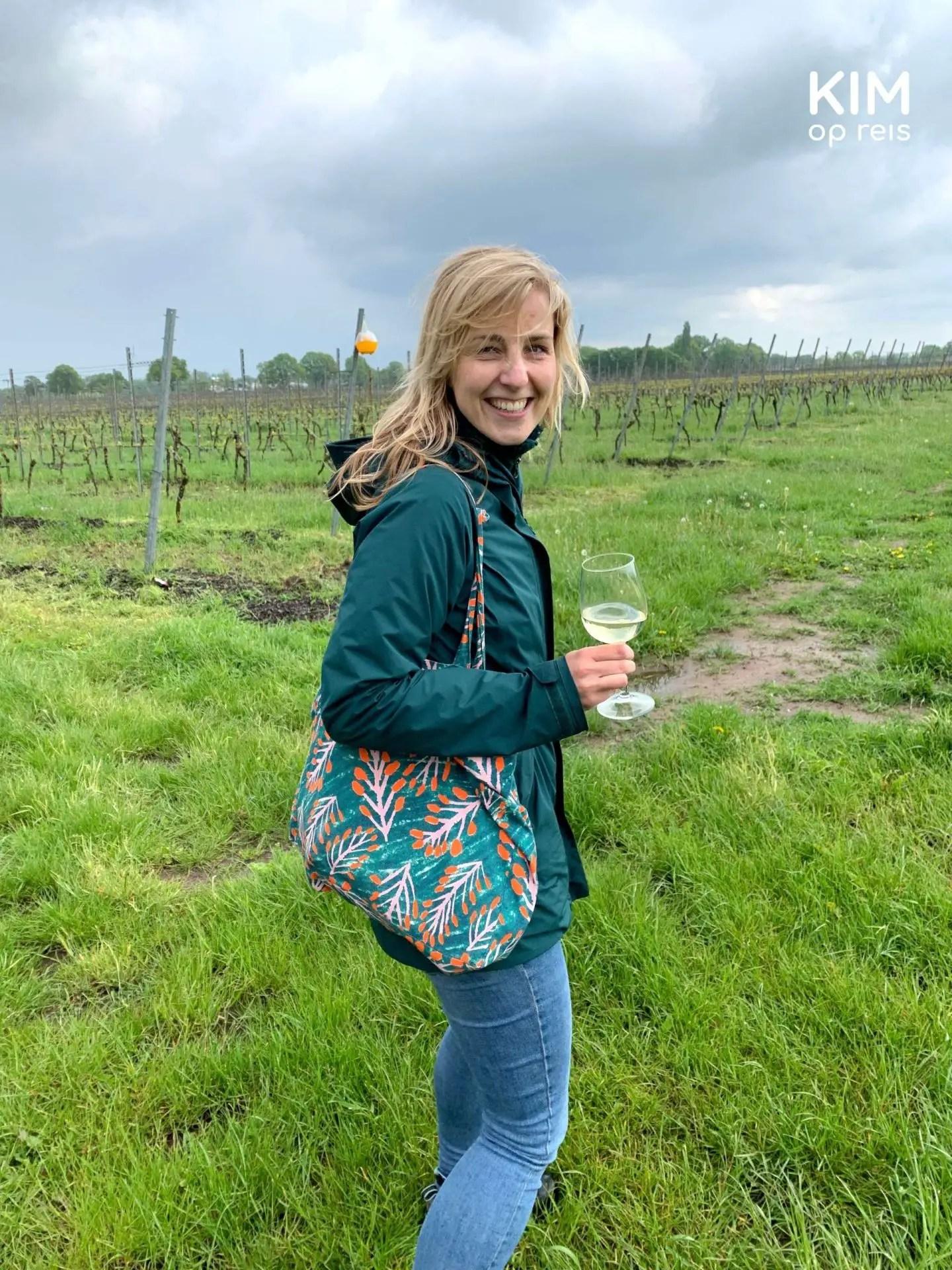 Wijnproeverij wijngaard De Wijnmakers: Kim loopt met glas witte wijn door de wijngaard