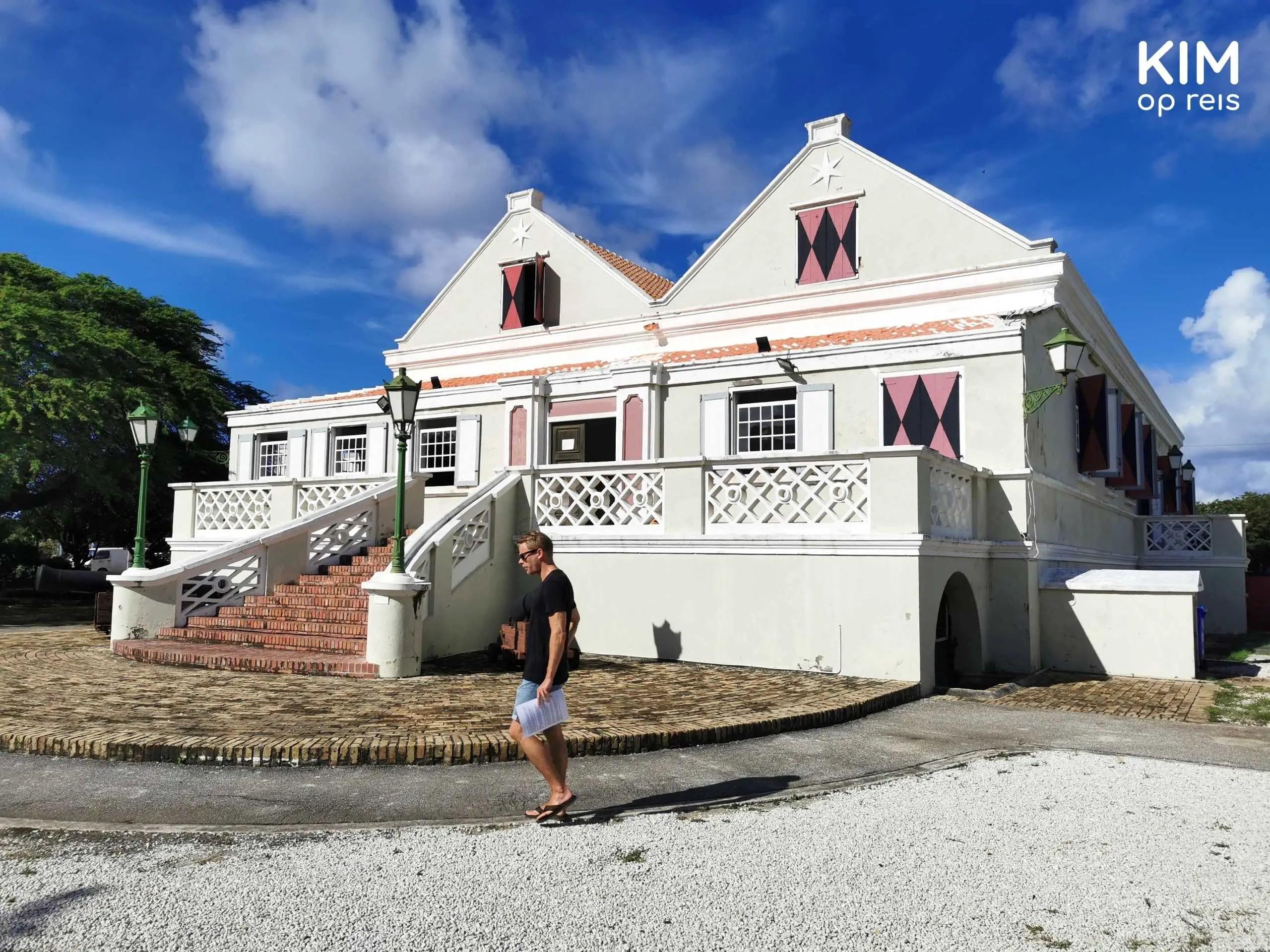 Curacaosch museum Willemstad: jongen loopt voor het museum langs, een lichtgekleurd koloniaal gebouw met luiken