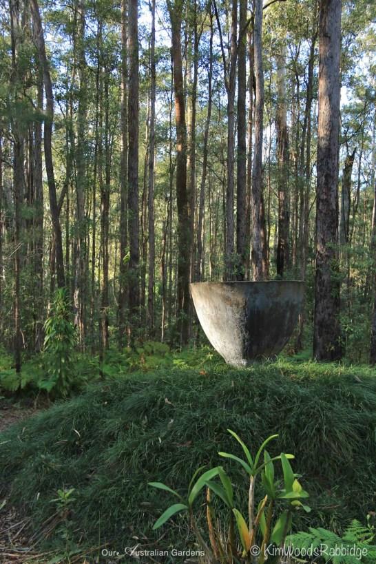 Earthenware bowl sits atop a mondo grass mound