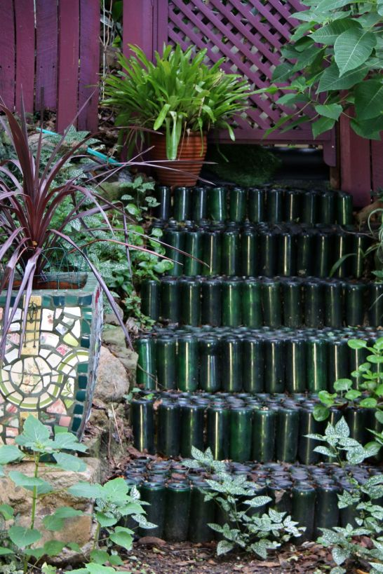 Stacked, upended bottles form steps at the back of the garden.