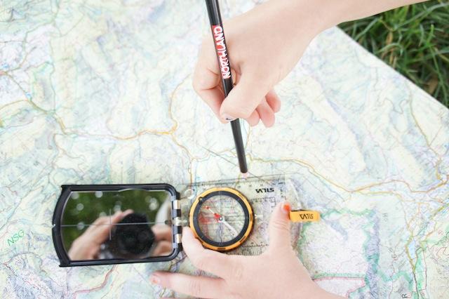 Kinder arbeiten mit Karte und Kompass: Den gemessenen Winkel übertragen sie auf die Karte um den Standort zu ermitteln. foto (c) kinderoutdoor.de