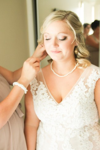Bride in beautiful pearl necklace gets help with her earrings