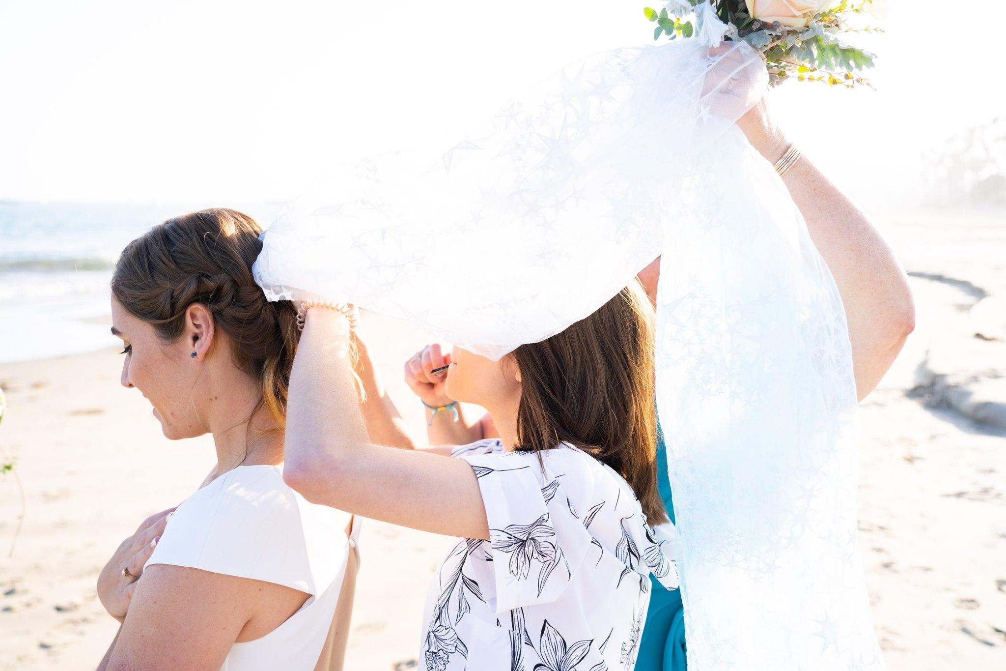 Wedding planner helping bride with veil