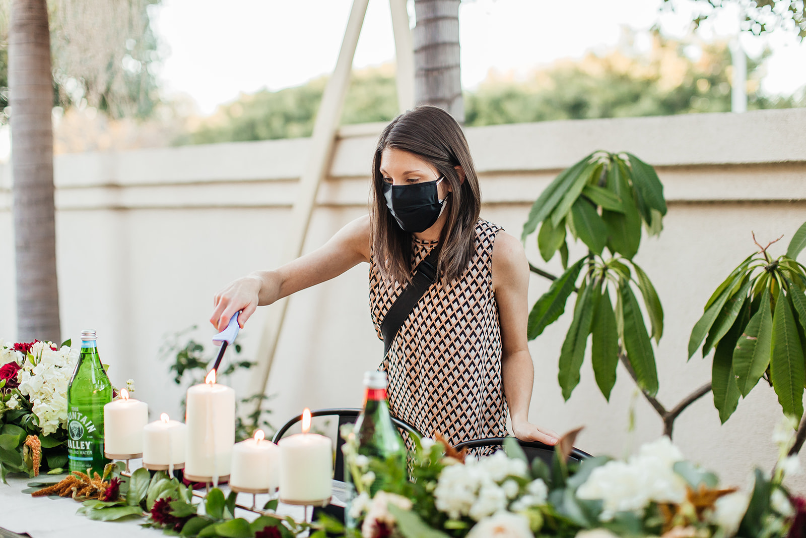 Wedding Planner in mask lights candles on tables