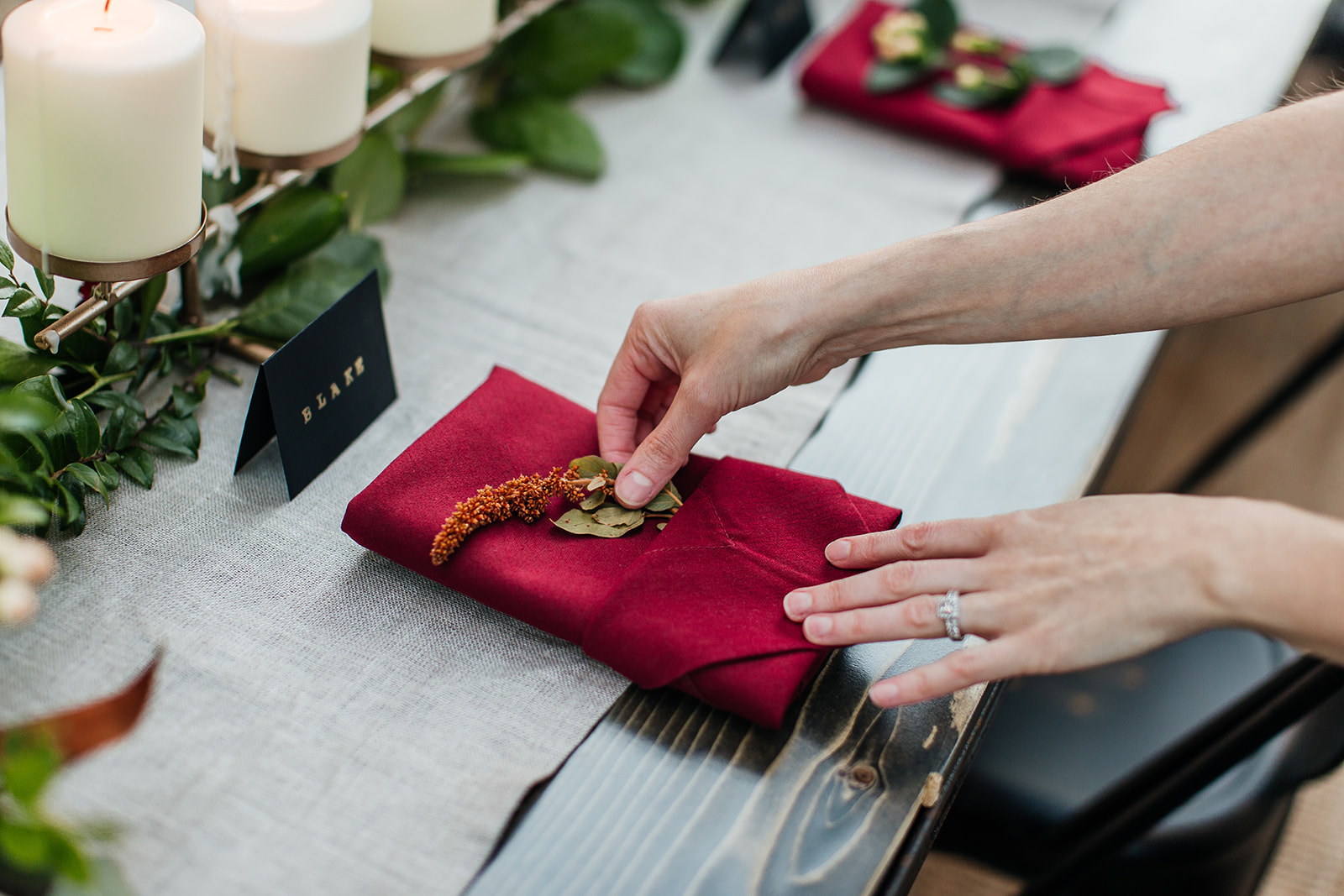 Wedding planner places florals in napkin placesetting