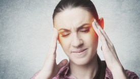 Sad frowning woman with headache touching her temples