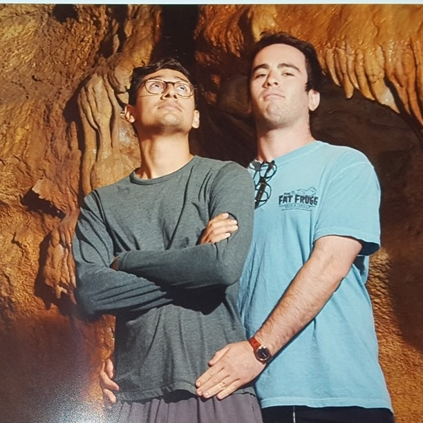 two very close friends and interracial business partners pose in a cave in colorado