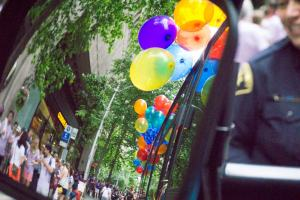 sideview of pride parade from bus mirror with balloons