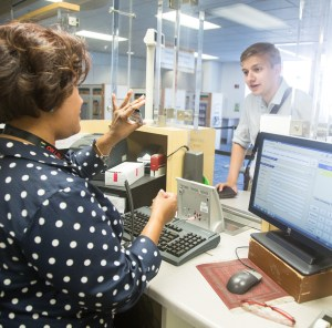 Sonja from Metro Customer Service holds up a bus pass while communicating with Nate using the loop counter system