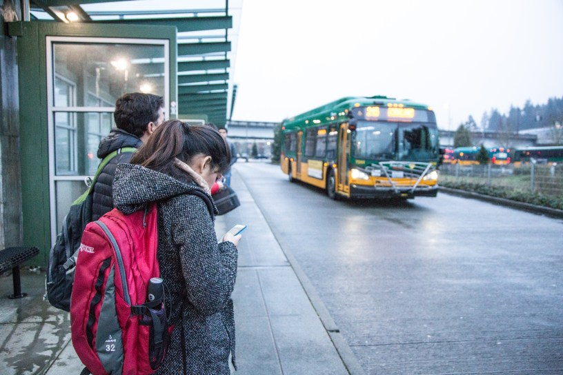 Rider looks at their phone while a bus approaches at a transit center