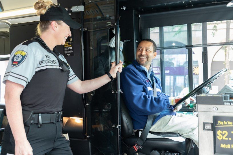Smiling fare enforcement officer chats with bus operator