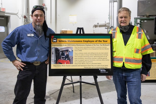 Equipment Service Worker Troy McDowell and Component Supply Center Superintendent Don Goodwin stand with a poster recognizing McDowell as Employee of the Year for King County Metro Vehicle Maintenance