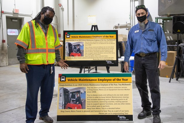 Equipment Service Worker Troy McDowell and General Manager Terry White stand with a poster recognizing McDowell as Employee of the Year for King County Metro Vehicle Maintenance