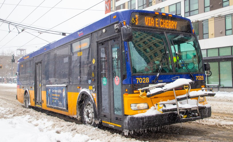 A chained and icy Metro bus travels in downtown Seattle in February 2021