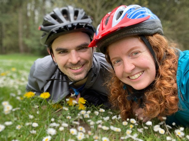 Bike enthusiasts Aaron and Elina smile in a meadow while wearing helmets