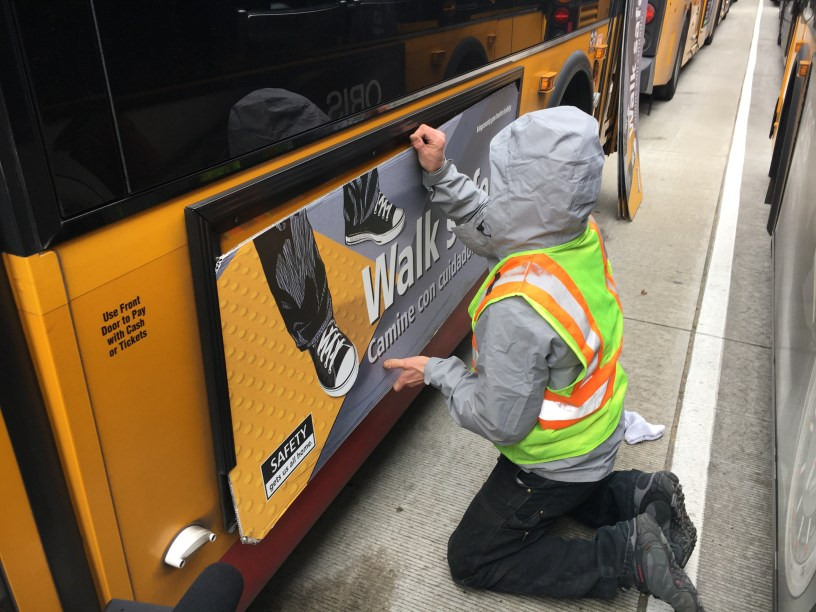 A worker installs advertising on the side of a bus