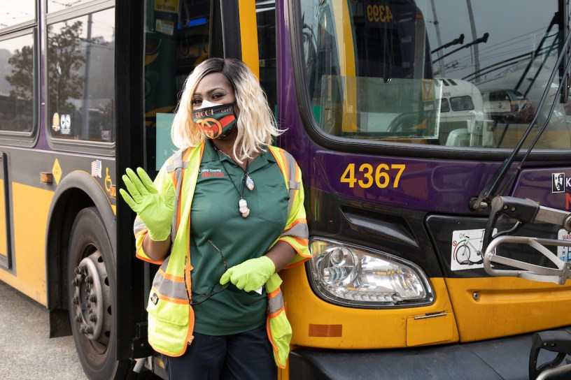 Transit operator Renita WRight wearing a mask and leaning against a purple and yellow trolley bus