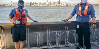 Water taxi crewmembers with view of Seattle across Puget Sound