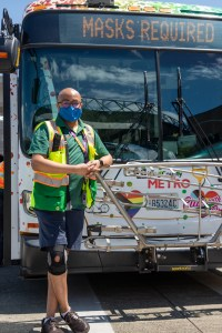 Front view of employee and Metro's Pride bus, with Pride progress flag, hearts and rainbow colors