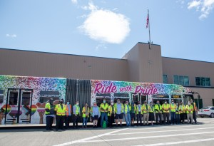 Side view of employees and Metro's Pride bus, with Pride progress flag, hearts and rainbow colors